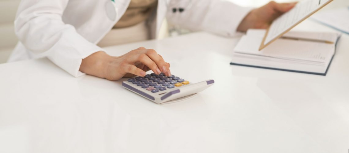 Closeup on medical doctor woman using calculator